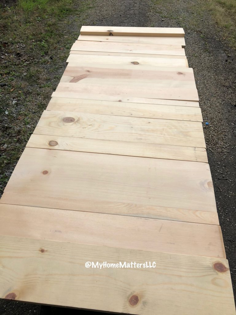 pine boards laid out on the ground to make a headboard