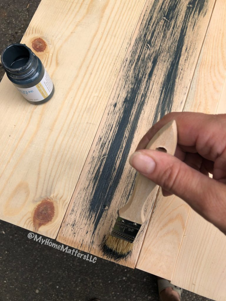 applying black paint to raw headboard with chip brush