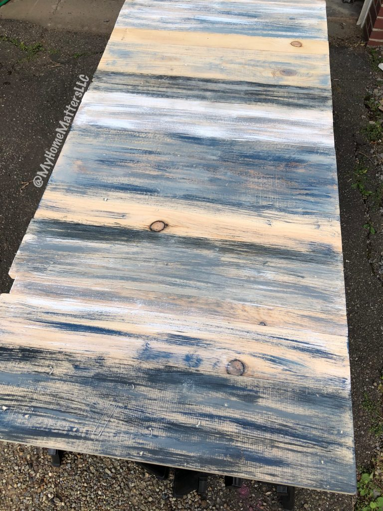 rustic wooden headboard dry brushed with blues and blacks and whites