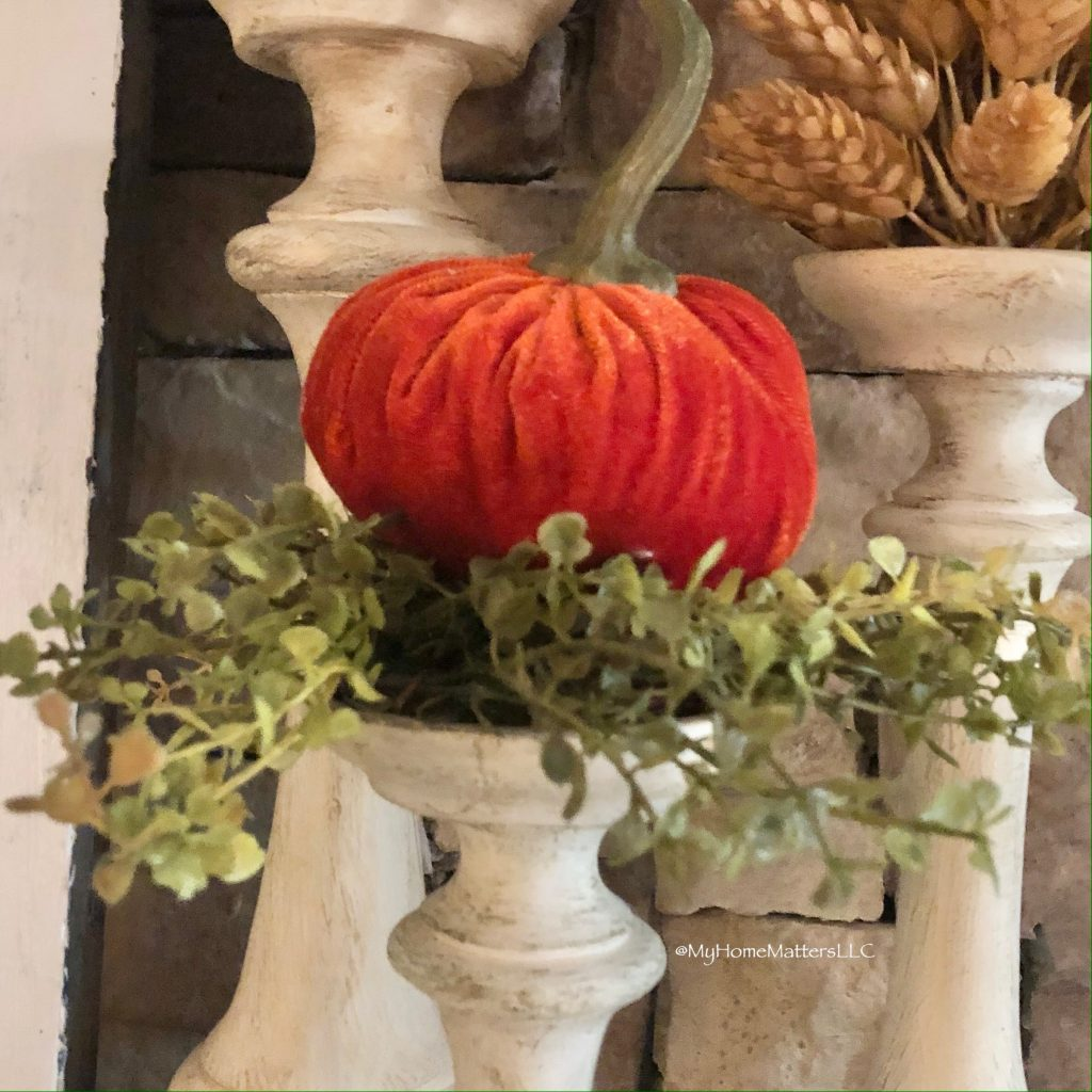 orange pumpkin on top of greenery on candle holder