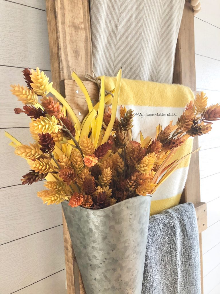 fall stems inside a tin hung from a blanket ladder
