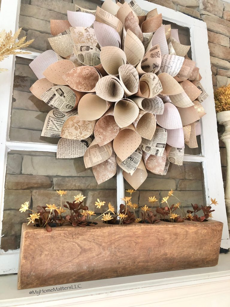 paper dahlia wreath and sugar mold on a mantel decorated for fall
