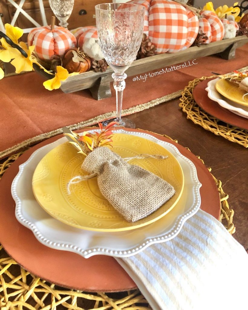place setting decorated for fall using yellow and orange