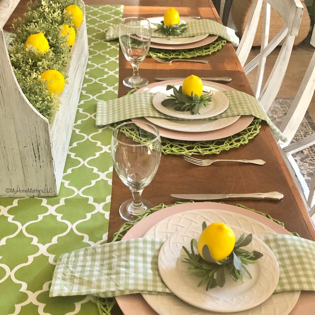 a summer table decorated with lemons and green and yellow decor