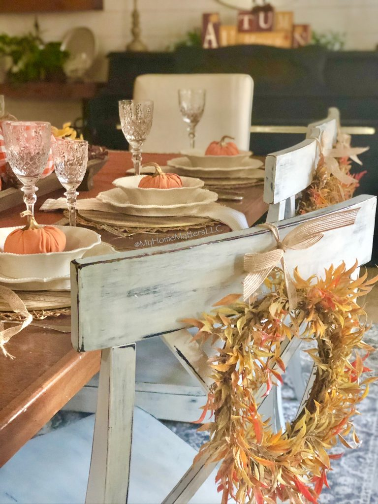 a Fall table and chairs decorated with Fall wreaths and pumpkins