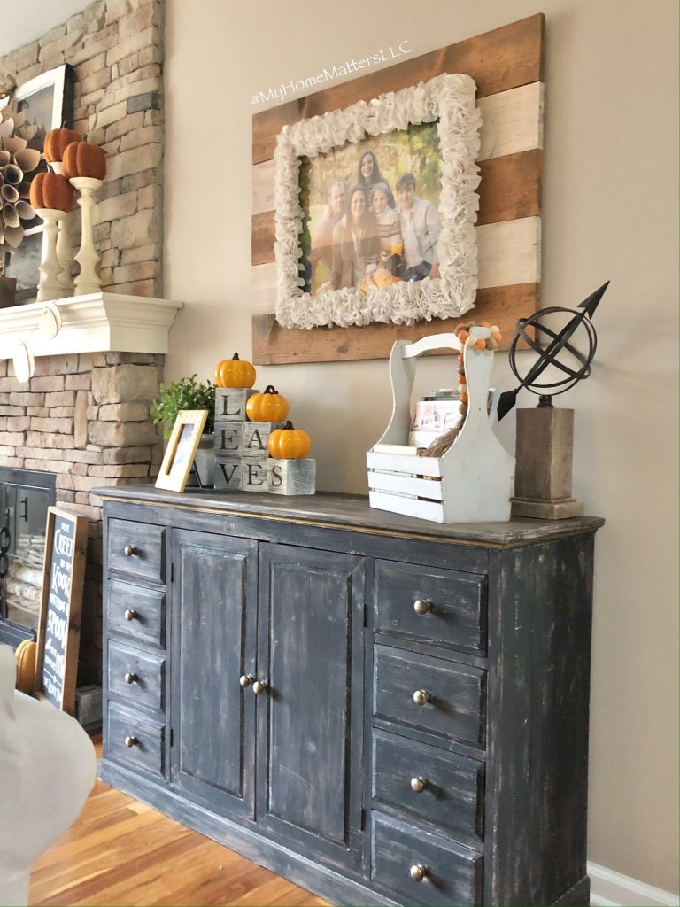 a black console table in a living room decorated for Fall