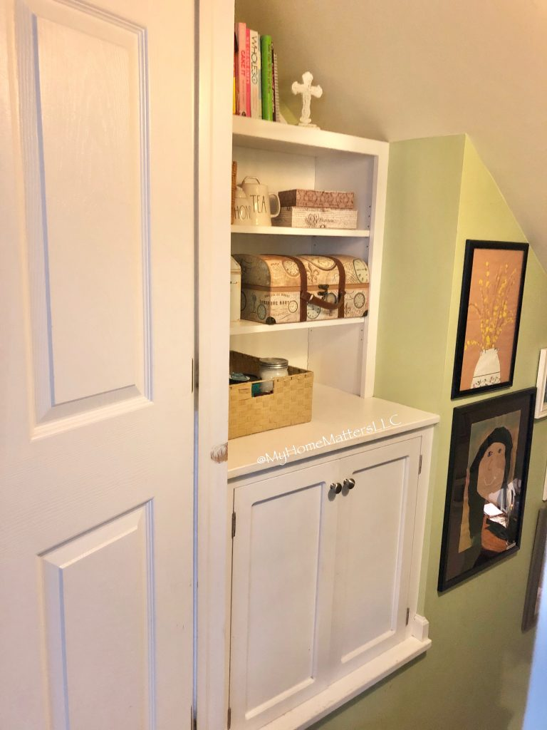 a built in cabinet in a stairwell decorated with bins and baskets