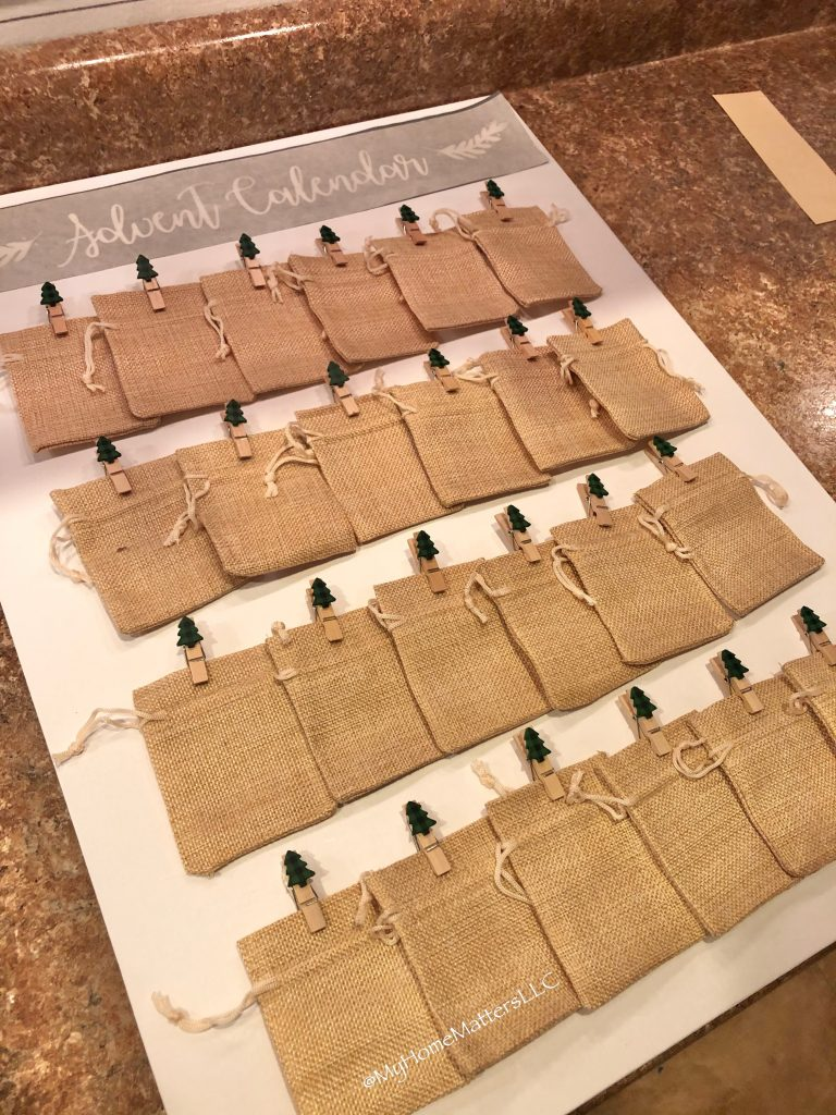 mini burlap sacs laid out on canvas to show how to make an advent calendar