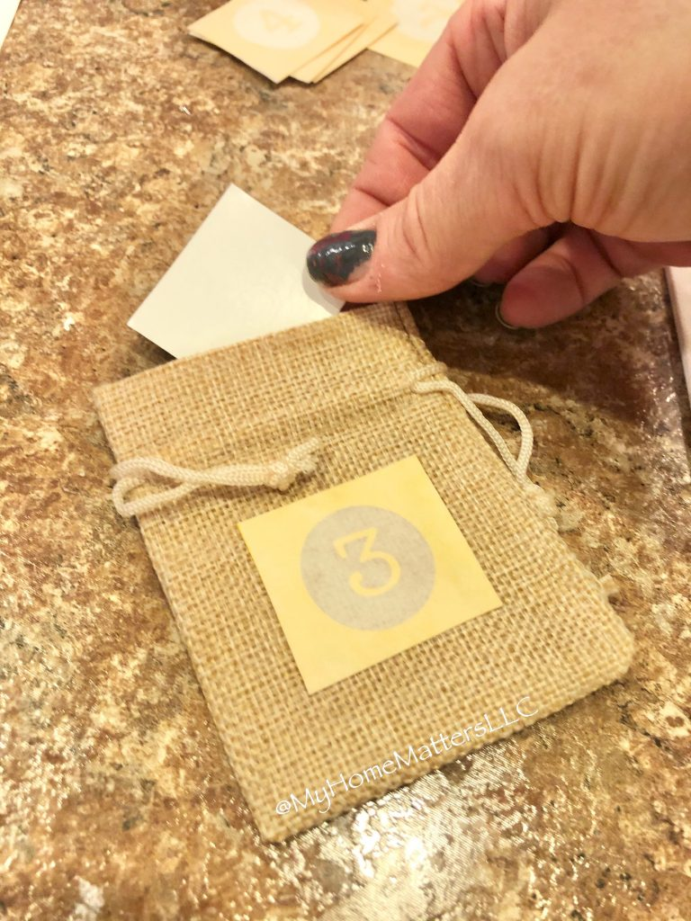 to show someone applying a number stencil to a small burlap sac