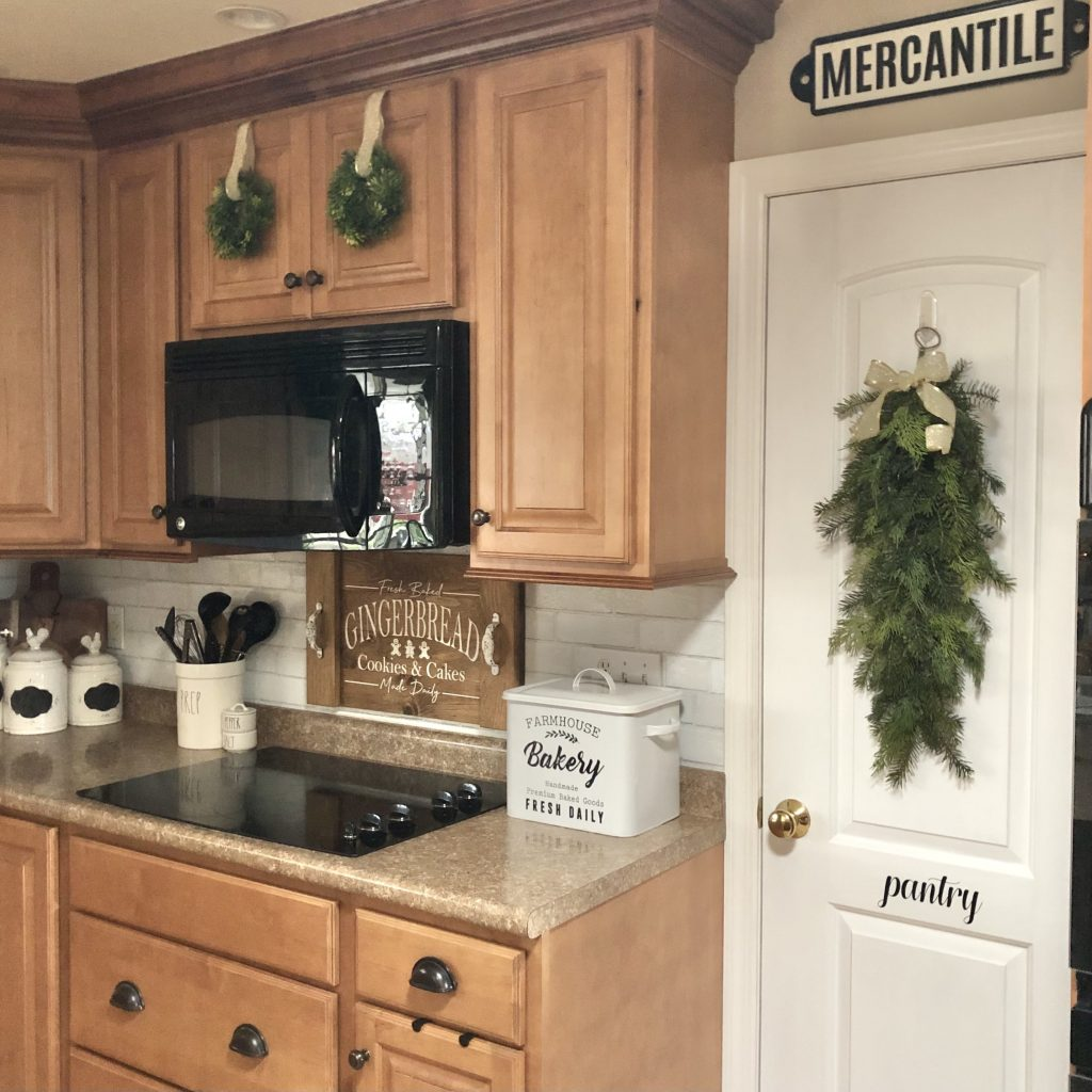 kitchen view of stove and pantry door to show use of greenery for Christmas decor