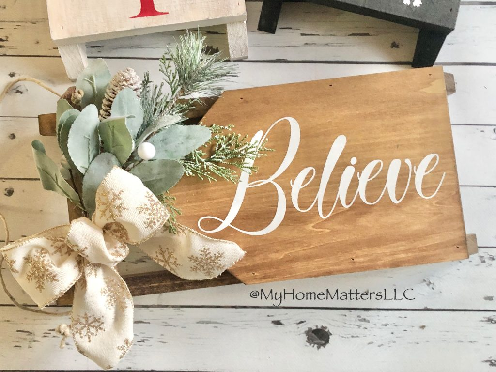 """small DIY wooden sled done in brown and white and gold that says """"Believe"""""""