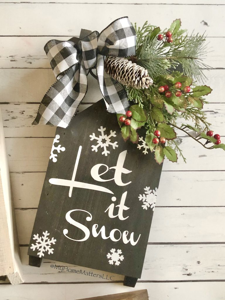 small sled in black that says Let it Snow