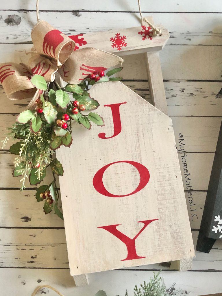 DIY wooden sled done in red lettering that says JOY